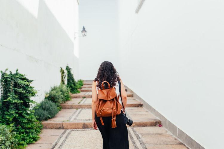 Rear view of woman walking on walkway amidst walls