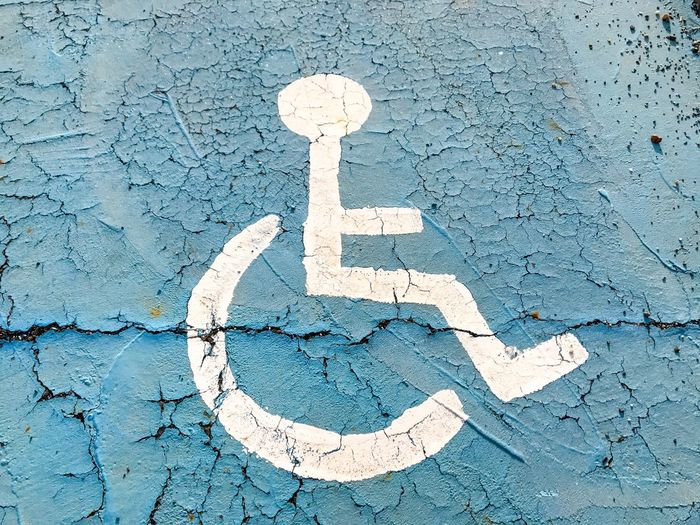 Close-up of disabled sign on weathered wall