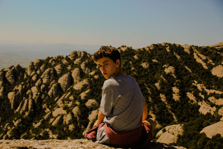 Boy Sitting On Rock Against Clear Sky