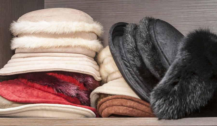 A heap of feminine winter hats are on a shelf. Close-up Warm Clothing Hats Hat Women Hat Clothes Fashion Objects Warm Hats Winter Hats Winter Fashion Style Style And Fashion Shelf Store Shelf Clothes Shop Hat Shop Hat Shopping Colorful Closeup