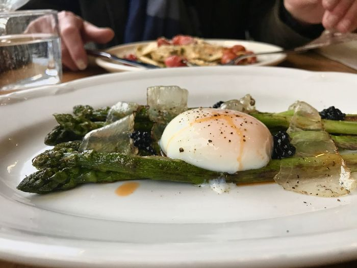 Close-up of poached egg with vegetables against man having food served on table