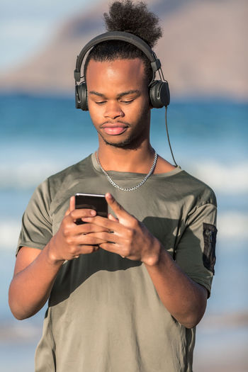 Handsome African American guy in modern headphones browsing smartphone and listening to music while standing on blurred background of sea Technology Wireless Technology Communication Telephone One Person Young Adult Using Phone Smart Phone Mobile Phone Leisure Activity Portable Information Device Lifestyles Focus On Foreground Listening Real People Connection Holding Front View Casual Clothing Outdoors Headset Man Listening To Music Music African American