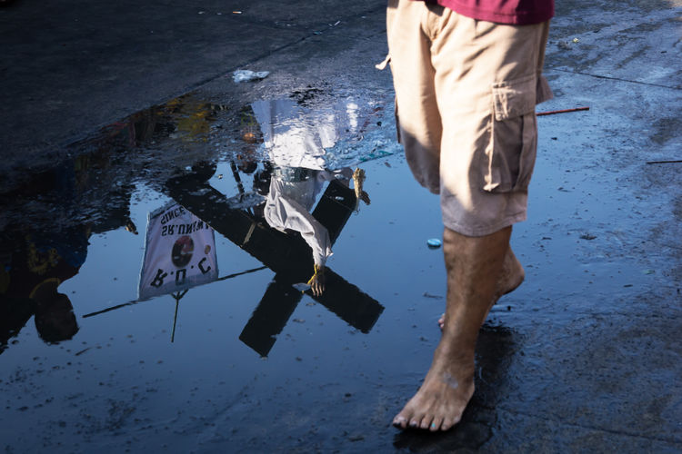 Low section of man standing on puddle