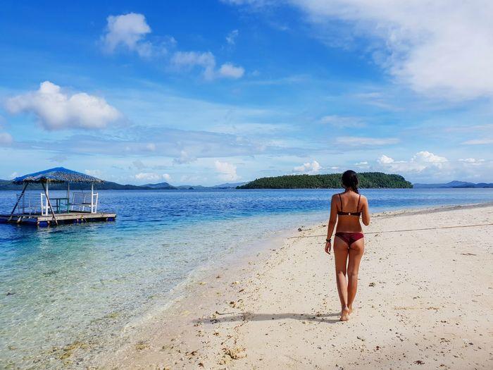 Full length rear view of woman wearing bikini while walking at beach