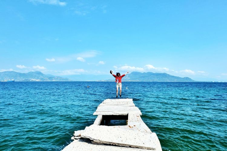 Woman Jumping On Old Pier On Sea Against Blue Sky