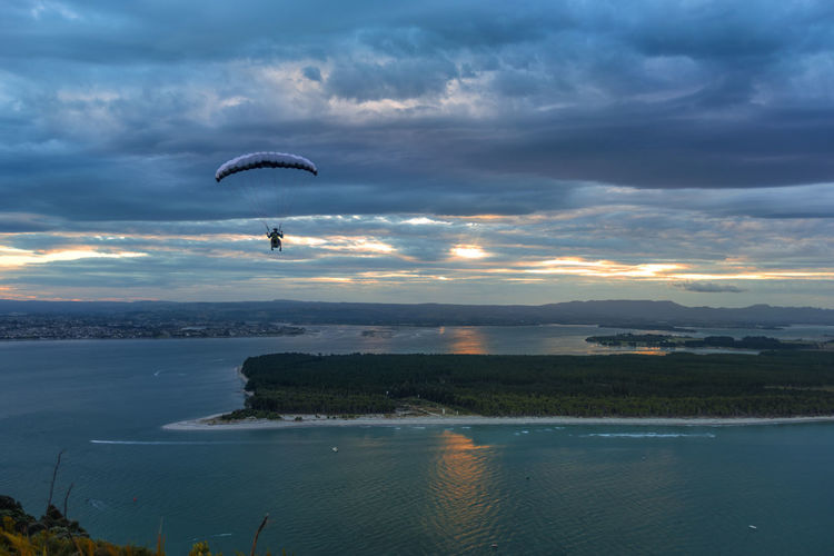 Person paragliding over sea against sky during sunset
