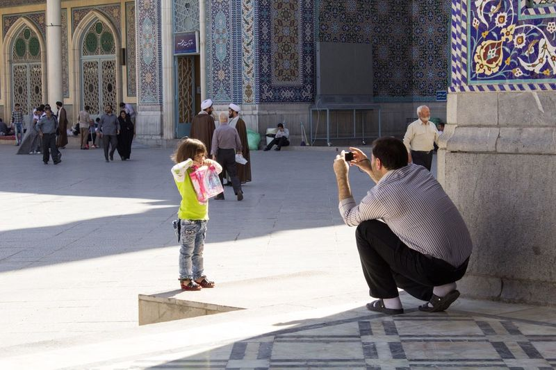 TwentySomething Picture of a man portrayed his daughter souvenir photo inside the shrine of Fatima in the Iranian city of Qom. Iran Qom