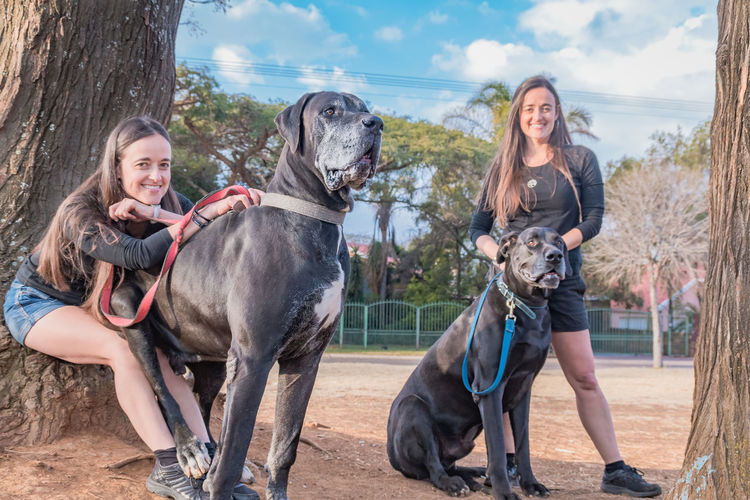Portrait of smiling sisters with dog on footpath against trees