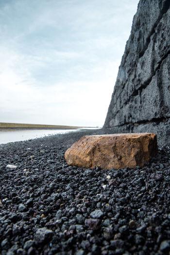 Surface level of rocks on beach against sky