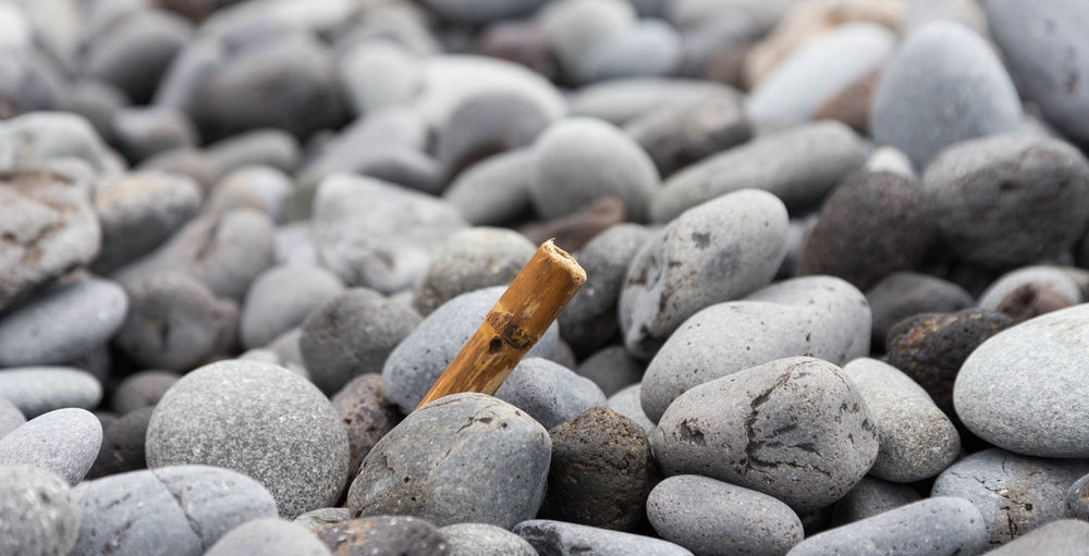 Close-Up Of Cigarette On Pebbles