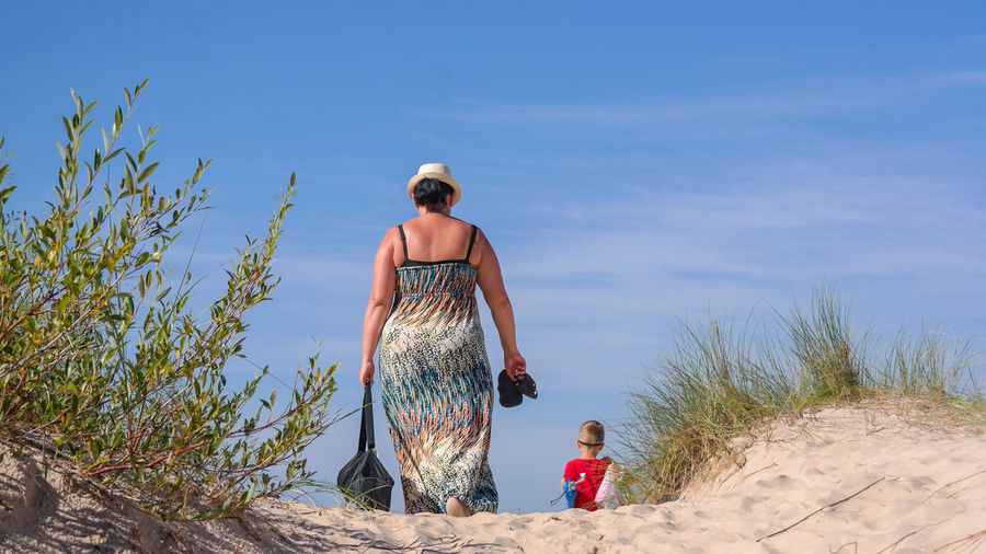 Rear View Of Mother And Son Walking At Beach Against Blue Sky