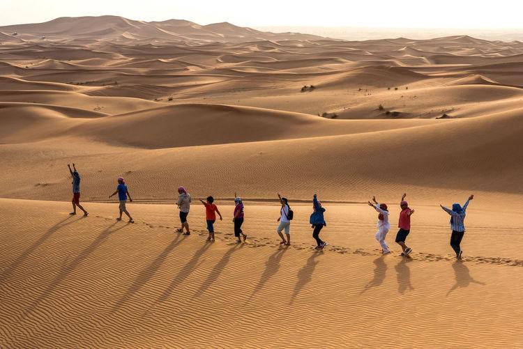 People on sand dune in desert