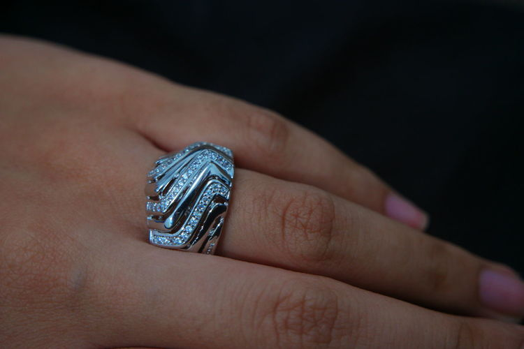 Close-up of woman showing ring against black background