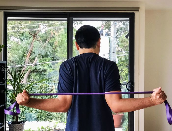 Rear view of man doing resistance band exercises.