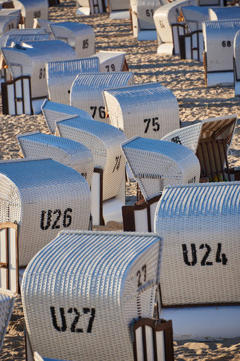 Hooded Beach Chair Chair Seat Land In A Row Beach No People Day Nature Water Sand Blue Text Number Absence Sea Travel Sunlight Outdoors Large Group Of Objects
