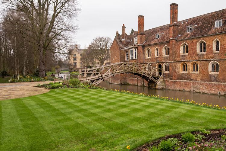 The mathematical Bridge also known as the Wooden Bridge designed by William Etheridge crossing the River Cam to connect 2 parts of Queens' College in Cambridge, UK. Mathematical Bridge River Cam Architecture Bridge Building Building Exterior Built Structure Cambridge Day Grass Green Color History Lawn No People Outdoors Plant Sky The Past Travel Destinations Tree University Water