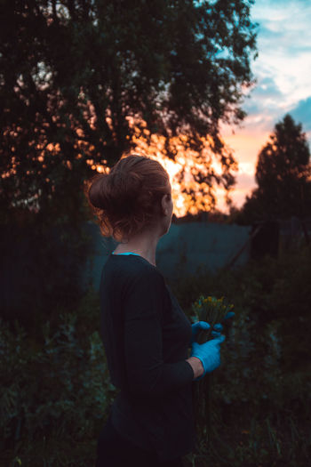 Side view of woman looking at sunset