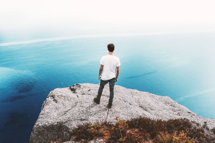 Rear View Of Man Standing On Cliff By Sea Against Sky