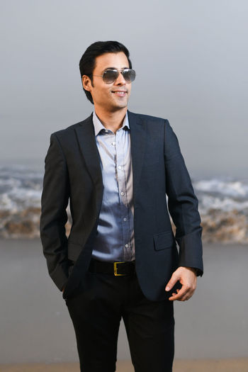 Young businessman standing at beach