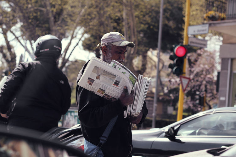 Cars Men Newspaper Person Poorpeople Red Light Rome Selective Focus Selling Selling News Selling On The Street Traffic Traffic Jam Traffic Lights The Photojournalist - 2018 EyeEm Awards