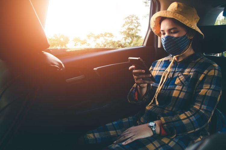 Man using smart phone in car