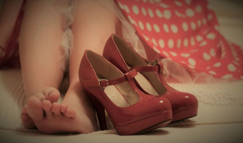 Low section of woman wearing high heels sitting on bed