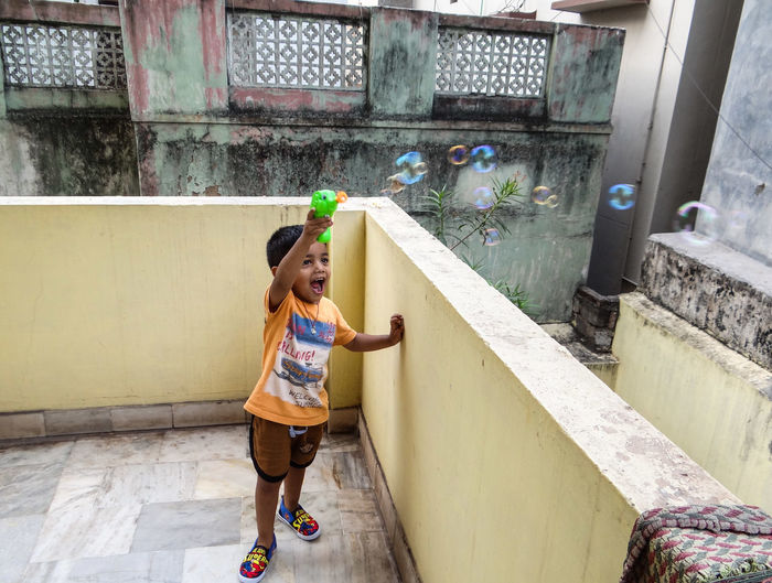 Boy playing with bubbles on terrace