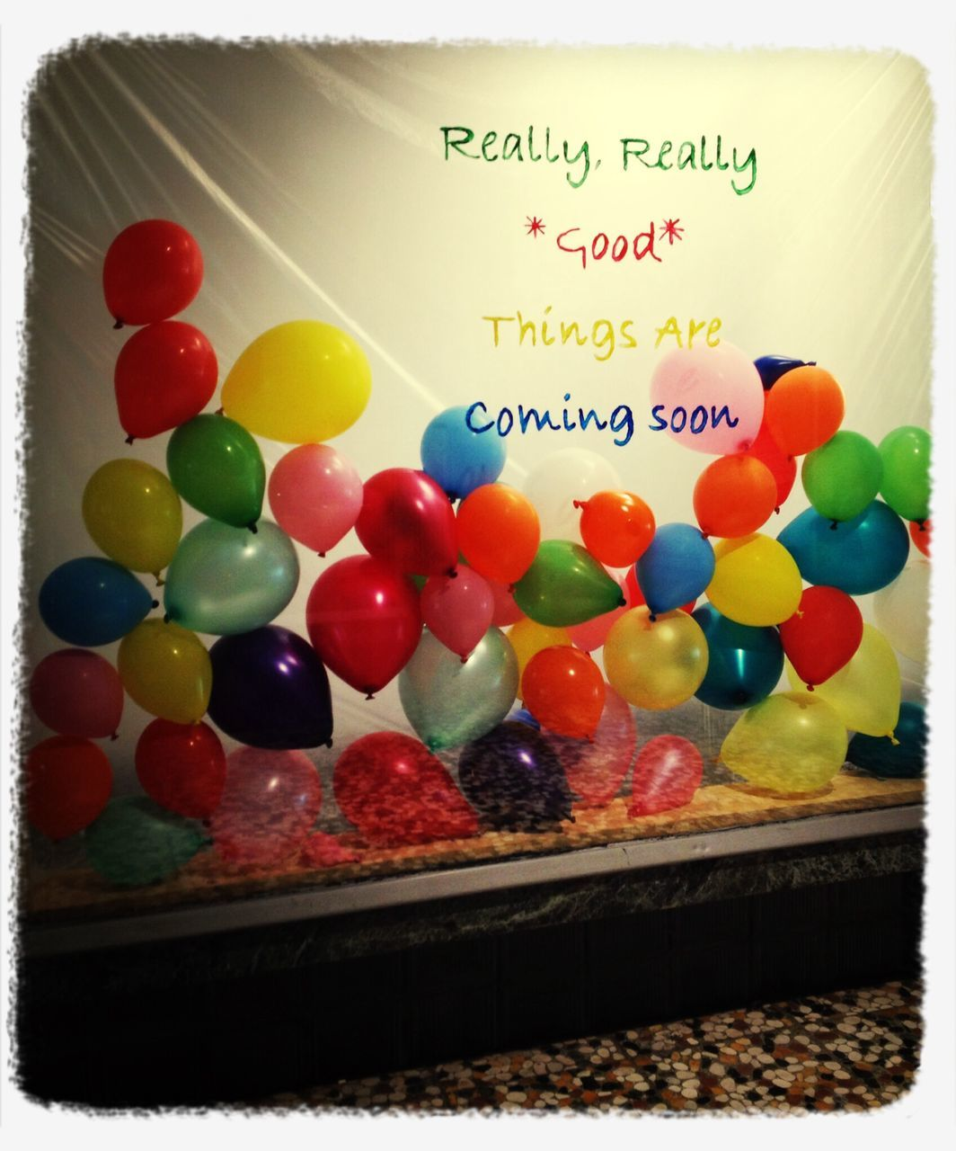 Multi colored balloons and text on window display