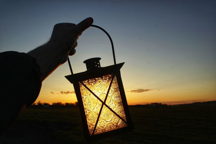 Cropped hand of man holding lantern against sky during sunset