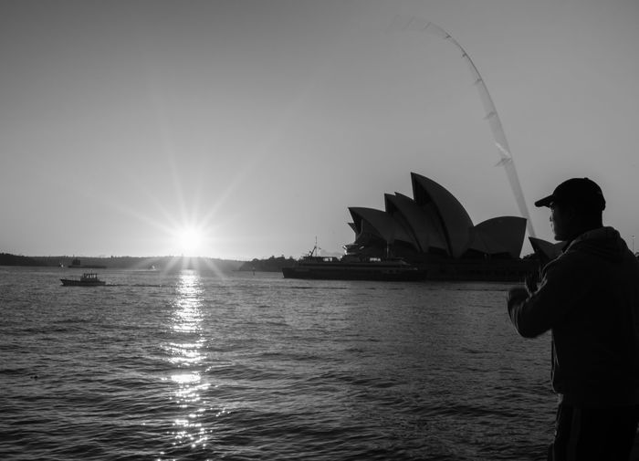 A Sydney Fisherman Reeling In The Sun Black And White Early Morning Fisherman Harbour View Morning Sky Ocean View Sunrise Sydney Opera House Monochrome Photography Waterfront Water_collection Sun Reflection Fishing The City Light