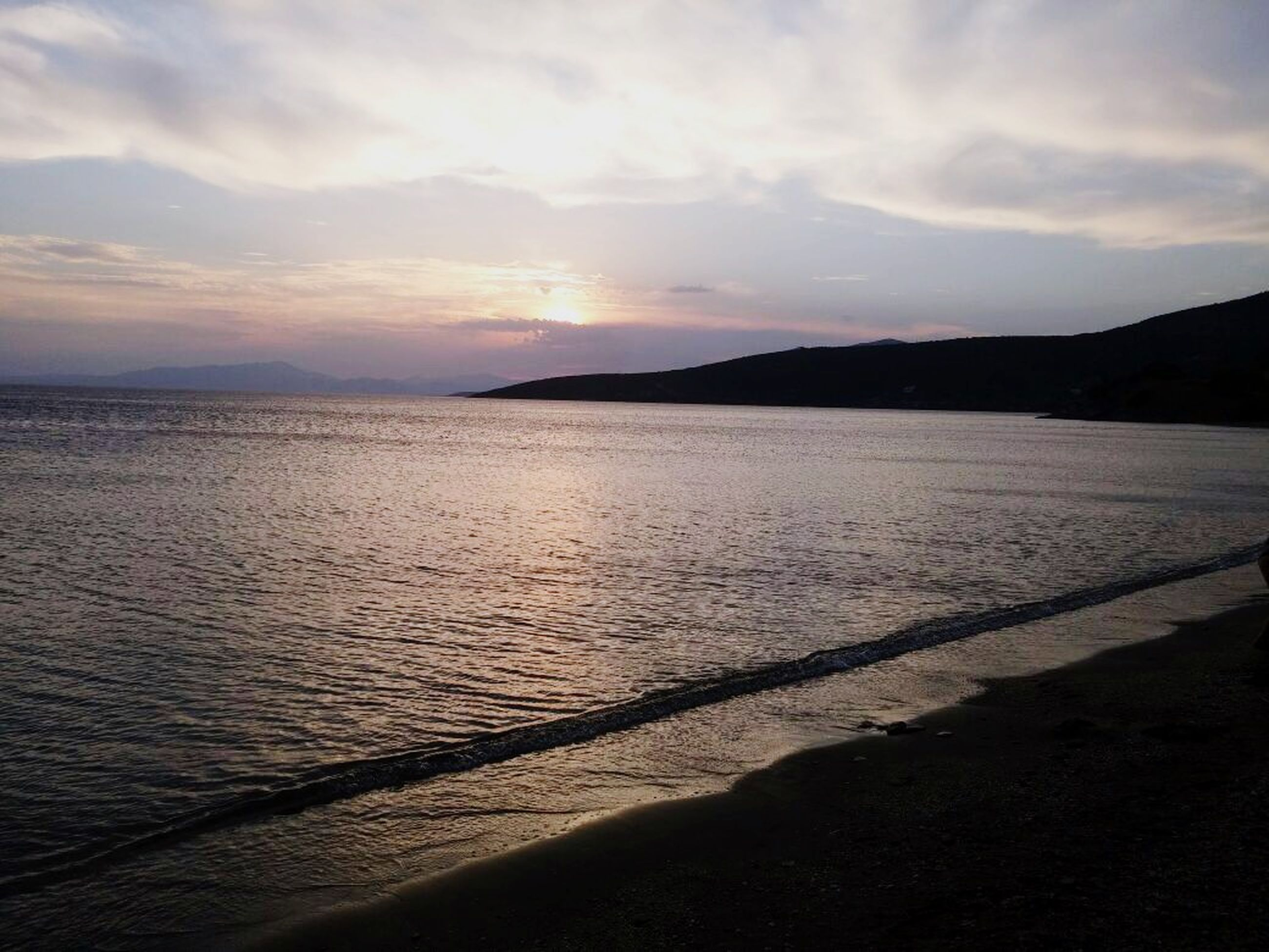 water, sunset, tranquil scene, scenics, sea, tranquility, beauty in nature, beach, sky, shore, nature, idyllic, sand, silhouette, coastline, cloud - sky, mountain, cloud, rippled, orange color