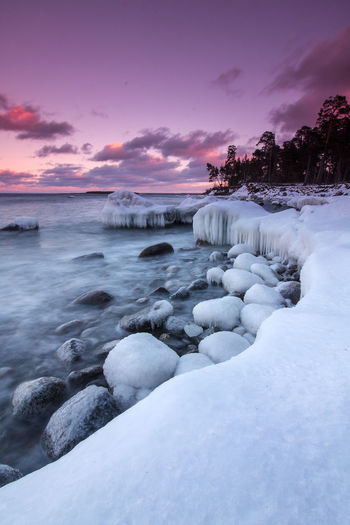 Scenic View Of Frozen Seashore Against Dramatic Sky
