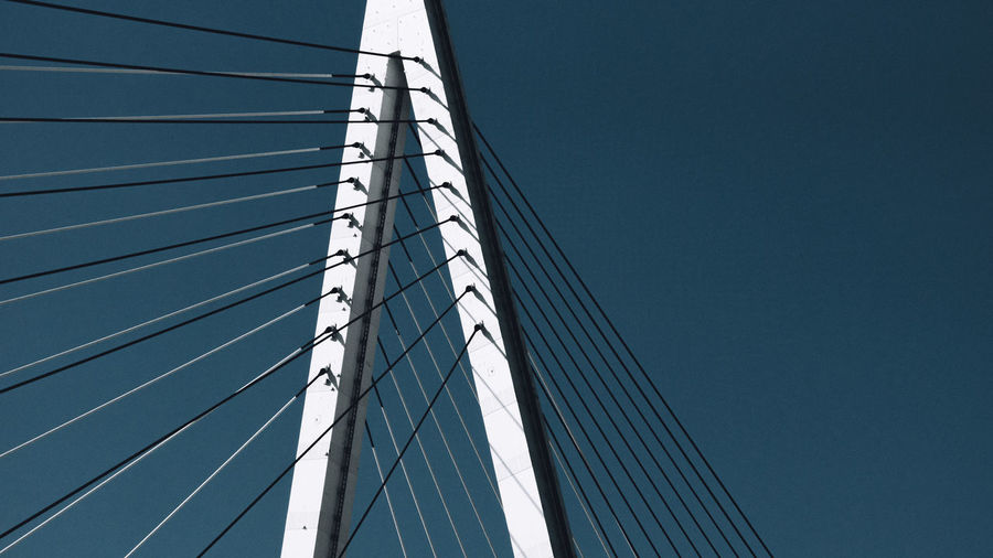 Low angle view of modern cable stayed bridge against clear blue sky