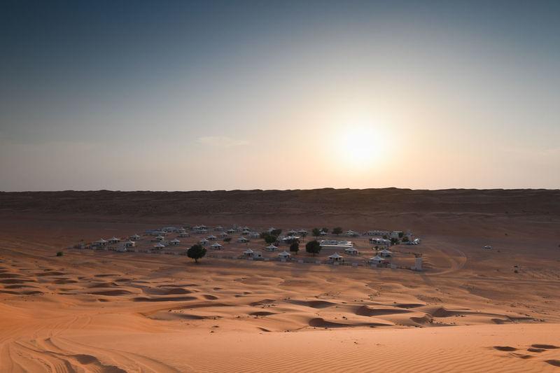 Buildings in desert against sky during sunset