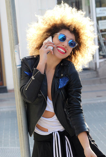 Portrait Of Happy Woman In Sunglasses Talking On Mobile Phone