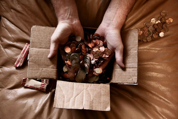 Cropped Hand Of Man Putting Us Coins In Cardboard Box