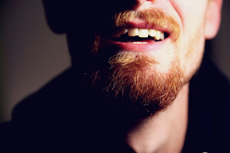 Cropped image of smiling bearded young man