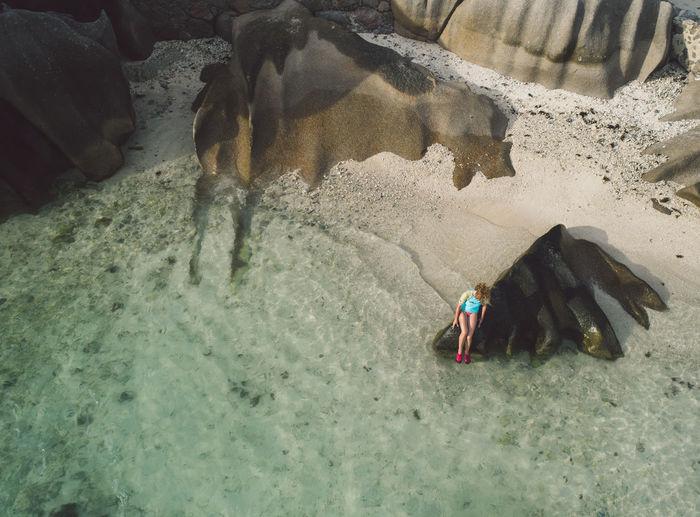 Woman sitting on rock in sea