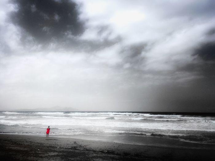 Distant woman on beach under overcast sky