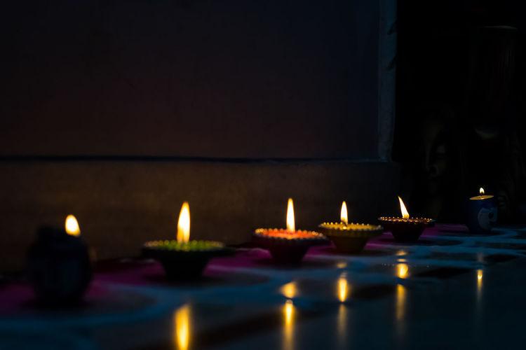 Illuminated tea light candles in building