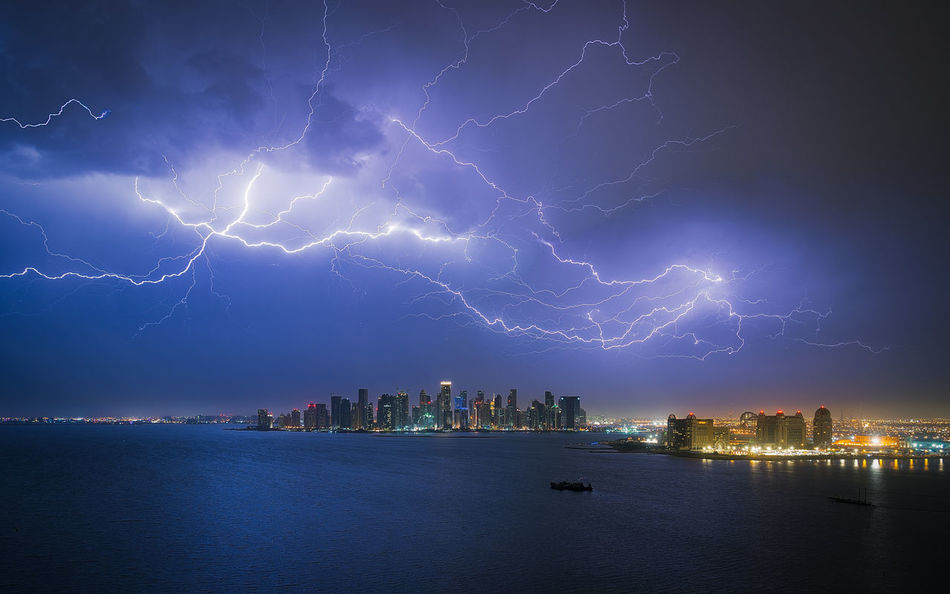"""While the sky lit up, many of the office towers in West Bay's skyline went dark - it happened to be """"earth hour"""" in Doha. Doha Earth Hour Westbay Building Exterior City Cityscape Katara Lightning Nature Night No People Qatar Scenics Sea Skyscraper Storm Storm Cloud Thunderstorm Urban Skyline Waterfront"""