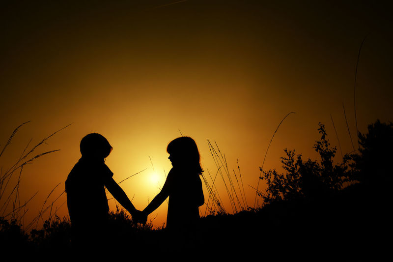 Silhouettes of a young boy and girl holding hands in the grass against a sunset or sunrise Adult Beauty In Nature Bonding Daughter Land Lifestyles Men Nature Orange Color People Plant Real People Scenics - Nature Silhouette Sky Standing Sunset Togetherness Tranquility Two People Women