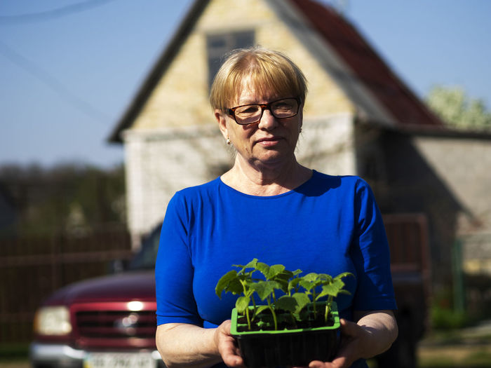 Senior caucasian woman is holds a container with cucumber seedlings. Seedlings Senior Women Caucasian Holds Container Cucumber Glasses Front View Eyeglasses  One Person Real People Focus On Foreground Waist Up Lifestyles Day Casual Clothing Architecture Built Structure Nature Portrait Holding Building Exterior Standing Plant Outdoors Gardening