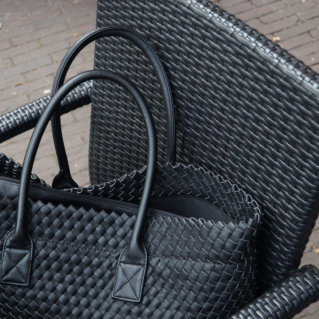 High Angle View Of Black Textured Purse On Wicker Armchair