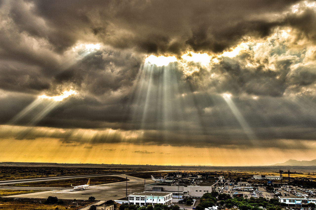 cloud - sky, sky, built structure, sunbeam, architecture, building exterior, sunlight, no people, outdoors, sun, scenics, nature, beauty in nature, sunset, cityscape, day, city