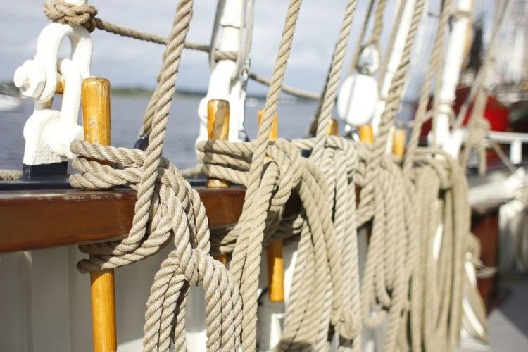 Close-up of rope tied on boat over lake