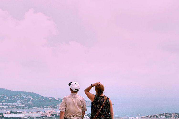 People standing by pink sea against sky in city