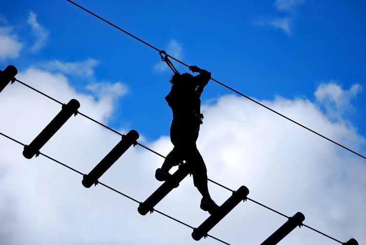 Low angle view of woman balancing on rope bridge