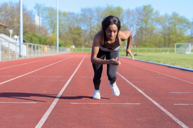 Young female athlete running on sports track