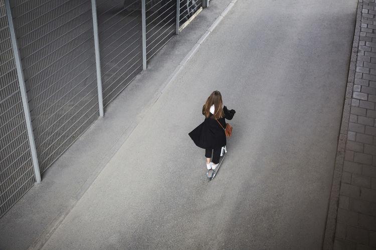 Rear view of woman walking on railing